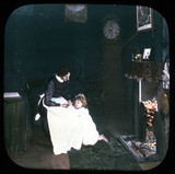 Woman and child in front of fire, c 1895.