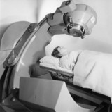 Female patient under radiotherapy machine, c 1953.