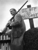 Farmer with gun sitting by 'Be Off or Be Shot' sign, 30 November 1967.