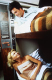 Couple in sleeping carriage bunk beds on BR train, c 1970s.