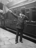 Passenger guard with a flag and whistle, c 1907.