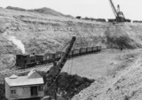 Train of iron ore tipplers in quarry with 0-4-0T and walking drag lines.