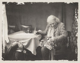Elderly man writing at a desk, c 1860s.
