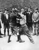 Boys fighting in the school playground, c 1930s.