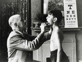 A doctor checks a young boy's tonsils, December 1935.