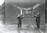 S F Cody (right) and another man holding a manlifting kite, c 1905.