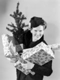 Woman carrying Christmas presents and tree, 1947.