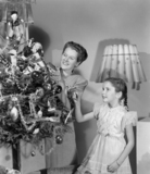 Woman and girl decorating a Christmas tree, c 1948.