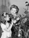 Woman and young girl by a Christmas tree, c 1950.