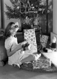 Little girl looking at Christmas presents, c 1950.
