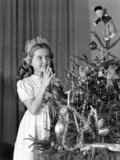 Little girl looking at Christmas tree, c 1950.