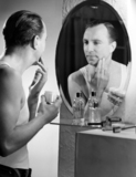 Man applying cream to his face after shaving, c 1950s.