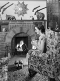 Woman knitting by the fire, c 1950.