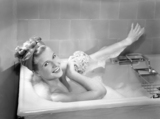 Woman lying in a foam bath washing herself with a sponge, c 1950s.