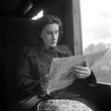 Woman reading a newspaper in a train carriage, 1950.