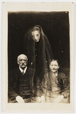 Elderly couple with a young female 'spirit', c 1920.