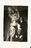 Family group with two 'spirits', c 1920.