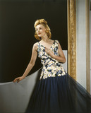 Model wearing a floral dress with net skirt, 1940s.