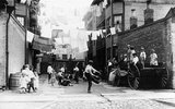 Children playing baseball in a tenement playground, USA, c 1913.