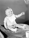 """Baby on a cushion, c 1950."""