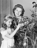 """Woman putting Christmas presents under the tree, c 1950."""