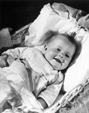 """A happy baby lying in a cot, 1940s. """
