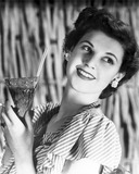 """Smiling young woman holding a drink, c 1940s."""