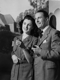 """Smiling couple outside a house, 1950."""