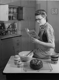 """Woman reading a recipe book in a kitchen, c 1950."""
