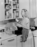 """Woman putting tins in the kitchen cupboard, 1952."""