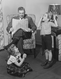 """Two children playing while a man reads a newspaper, c 1949."""