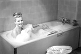 """Woman having a bubble bath, 1950."""