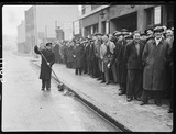 """Queue of unemployed men, Stepney, London, 1938."""