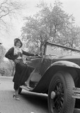 Young woman poses next to car. Photographed by Zoltan Glass, c.1930.