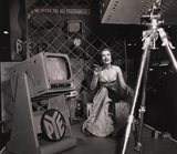 Miss Avis Scott poses in front of a 3d T.V Camera, 1954.