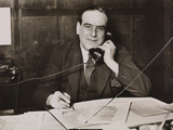 Gordon Helsby, newspaper editor, on telephone in office.