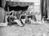 Three women modelling bathing costumes and a beach hammock
