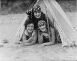 Three women wearing the latest summer fashions lying prone in a tent, c 1920s.