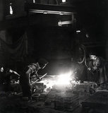 Works photographic negative showing steel foundry employees pouring molten steel, 1945.