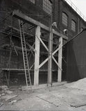 Works photographic negative of exterior view of the boiler shop showing a new doorway being made in the wall, 1960.
