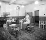 Works photographic negative of interior view of the ambulance room with staff nurse, 1940.