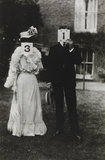 A couple, each holding up a number in front of their face circa 1905
