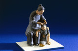 Figurine of a Chinese woman examining a child for head lice.