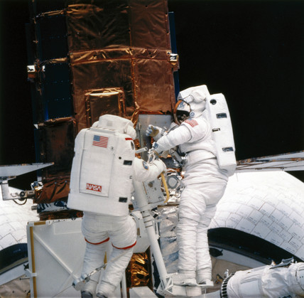Shuttle astronauts repairing the Solar Maximum Satellite, 1984.