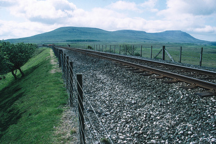 Single railway line, with men working in the distance.