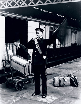Photograph of a guard with whistle and flag at Euston Station, London, signalling the departure of a London & North Western Railway (LNWR) train.
