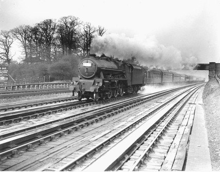 LMS expres at Bushey troughs picking up water, c 1920s.