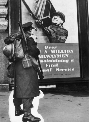 Soldier standing in front of a poster, Second World War, 1939-1945.