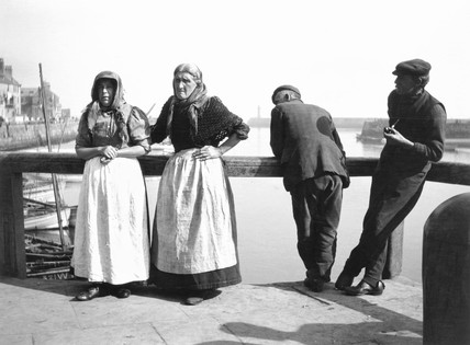 Four fisherfolk standing on a jetty in Whitby, North Yorkshire, c 1900s.