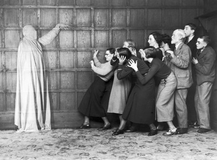 People 'cowering in fear' at the sight of a ghost, c 1920s.